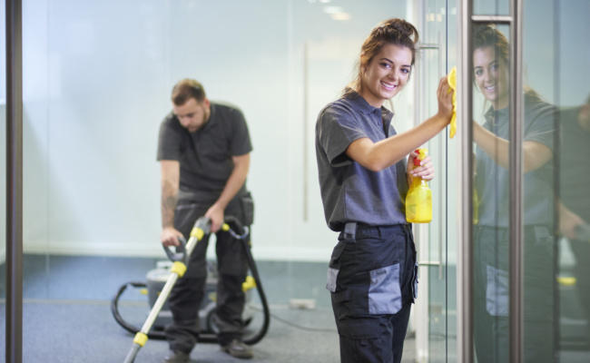 a female cleaning contractor is polishing the glass partition offices whilst In the background a male colleague steam cleans an office carpet in a empty office in between tenants.  .The female is smiling to camera.